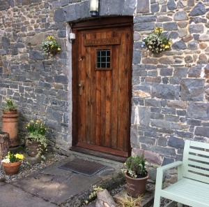 Front door of Lletty Cottage with newly stained  garden seat.