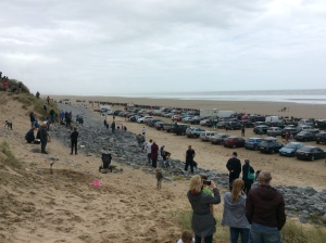Vast numbers of cars and spectators  on the beach to watch the cars make their runs.